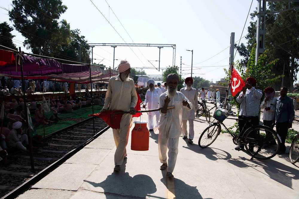 Farmers carry cartons of milk that they have brought from home for refreshments and tea. Sangrur, Punjab.