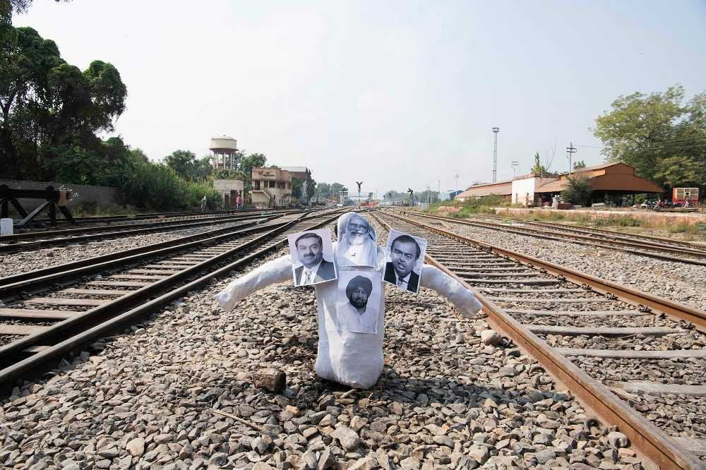An effigy which contains photographs of (from left to right) Gautam Adani, Narendra Modi, Captain Amarinder Singh, and Mukesh Ambani at the Firozpur junction in Punjab.