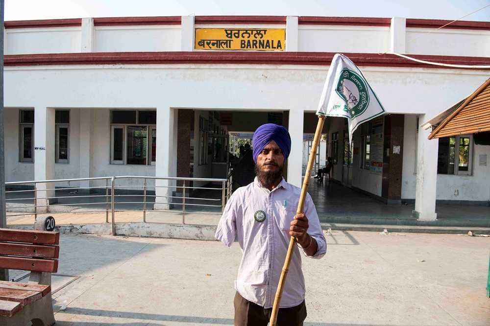 A farmer holds a flag of the Bhartiya Kisan Union (Dakonda). Barnala, Punjab.